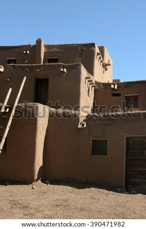Strong sun throws shadows on a traditional adobe dwelling at the Taos Pueblo in New Mexico. - stock photo