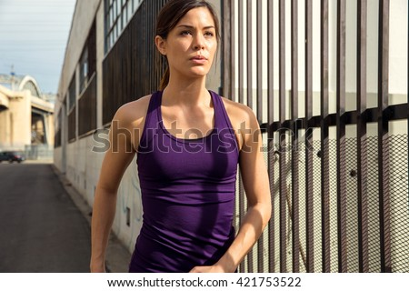 Strong tough muscular woman fit beautiful thin energetic city streets cardio exercise