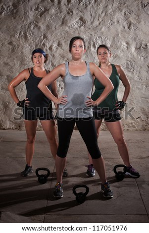 Strong trio of European women resting during boot camp workout - stock photo