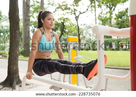 Strong Vietnamese woman performing L-sit exercise on parallel bars  - stock photo