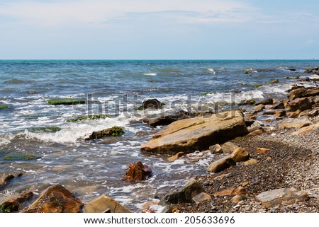 Strong wave splashing on the rocky shores  - stock photo
