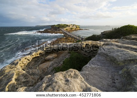 Strong wind at Bare Island Australia view from La Perouse with big rock hole in forground with afternoon sun and thin clouds in sky - stock photo