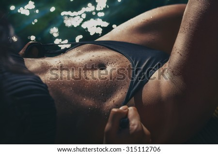 Strong woman abs with water drops on the sun by the sea