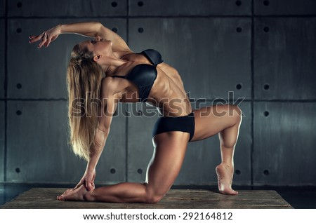 Strong woman bodybuilder on wall background. - stock photo