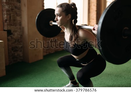 Strong woman lifting barbell at the gym - stock photo