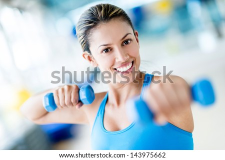 Strong woman weightlifting at the gym looking happy - stock photo