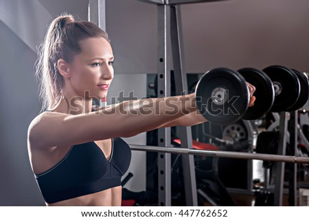 Strong woman weightlifting at the gym. Woman working out with dumbbells at a gym. Dumbbell bicep curl by a fitness girl. In good condition - stock photo