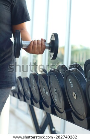strong women hand takes a heavy dumbbell in gym - stock photo
