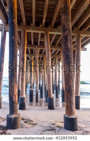 Strong Wooden Pylons underneath of Ventura Pier, city of San Buena Ventura, Southern California - stock photo
