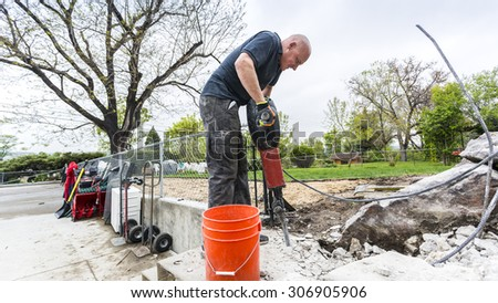 Strong worker using jackhammer in the yard