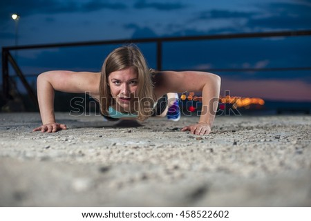 Strong young caucasian woman doing push ups or press ups on sea pier. Fitness workout outdoors - stock photo