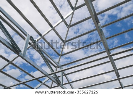 Structure of steel roof frame with blue sky and clouds at construction site - stock photo