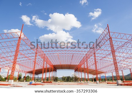 Structure of steel roof truss under building construction with blue sky  - stock photo