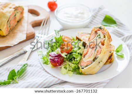 Strudel pie with salmon and spinach, served on white plate with salad, cherry tomatoes, sour cream, white wood background, closeup - stock photo