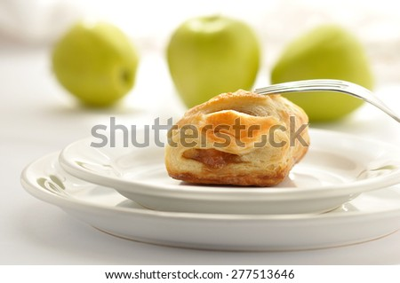 Strudel with apples on white background with apple slices - stock photo