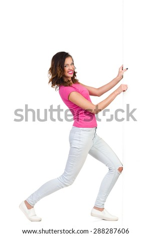 Struggle With A Wall. Young woman pulling a wall. Full length studio shot isolated on white. - stock photo