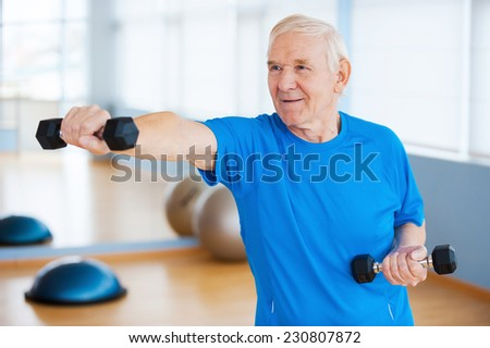 Struggling with age. Confident senior man exercising with dumbbells and smiling while standing in health club - stock photo