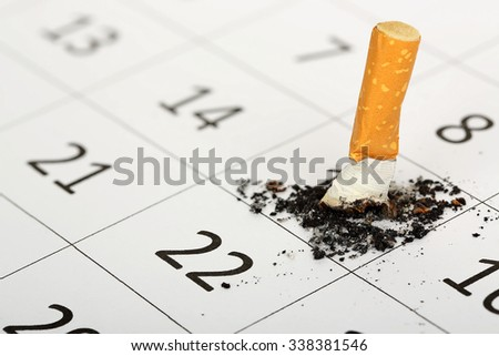 stubbed out cigarette on calendar, quit smoking concept