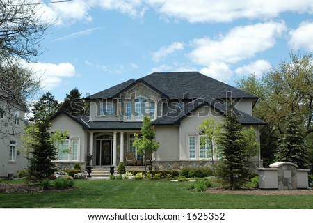 Stucco and stone house with pillars and bright blue sky with green manicured lawn / garden - stock photo