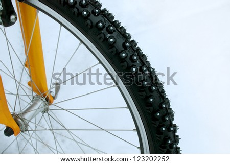 Studded bicycle tire with snow - stock photo