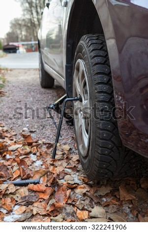 Studded tire wheel mounting on a car with jack-screw at autumn