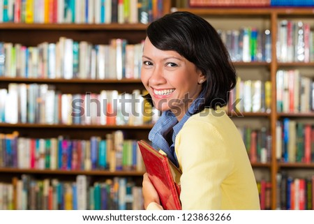 Student - a young Asian woman or girl learning in a library, she proudly holds a book or textbook