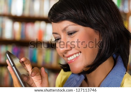 Student - a young Asian woman or girl learning in library and reading e-book on tablet computer - stock photo