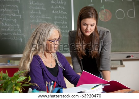 Student and teacher going through the homework that got handed in - stock photo