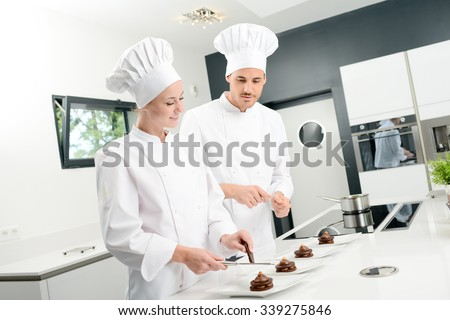 student and teacher in a professional cook school kitchen preparing a chocolate dessert - stock photo