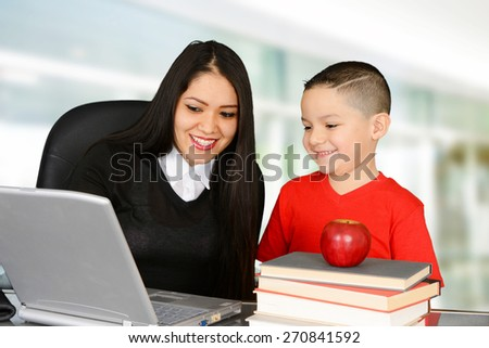 Student and teacher looking at laptop and smiling - stock photo