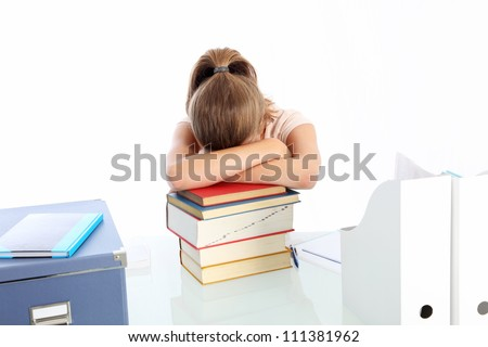 Student asleep on a pile of books Young woman student seated at her desk asleep on a pile of books worn out by overwork and stress