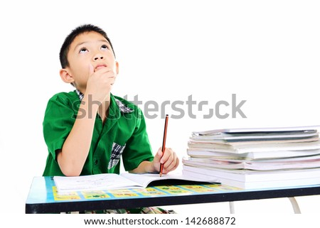 Student boy thinking about the answer on homework - stock photo