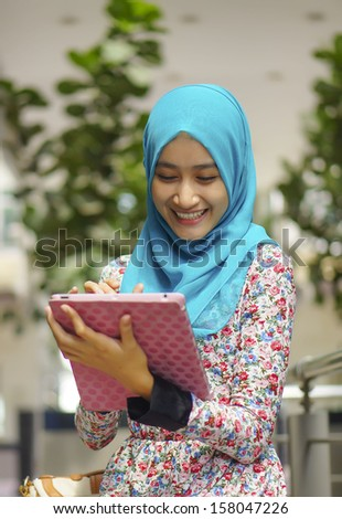 Student browsing the internet through her Digital Tablet outdoors  - stock photo