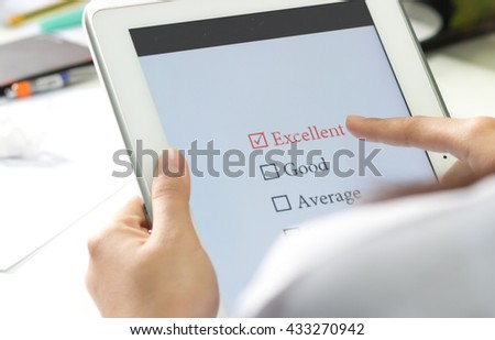 student checking in exercise, exams answer on a tablet with multiple-choice assessment by finger clicking - stock photo
