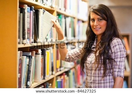 Student choosing a book while looking at the camera