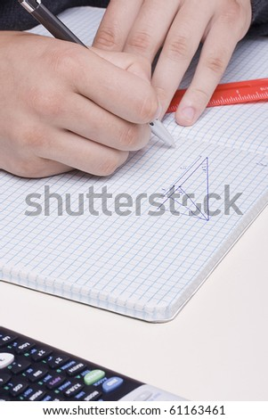 Student doing geometry problem in a notebook. - stock photo