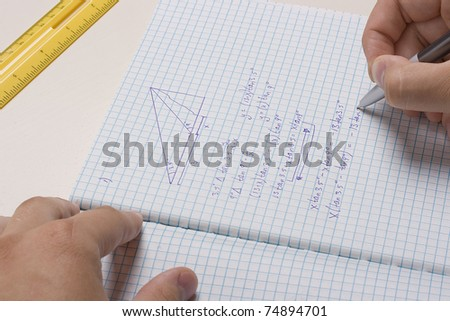 Student doing math homework in a notebook. - stock photo