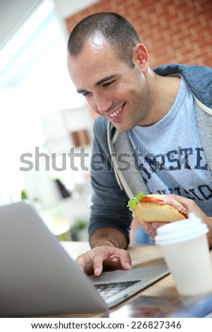 Student eating sandwich in front of laptop - stock photo