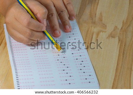 Student filling out and eraser answer sheets, exam paper on wood table - stock photo