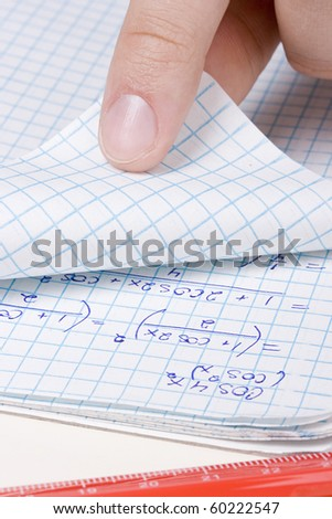 Student folding a page in a math notebook. - stock photo