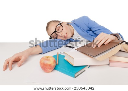 student girl in big glasses sit and sleep at the table with red apple, many colorful books, copybook and pensil, on  white background - stock photo