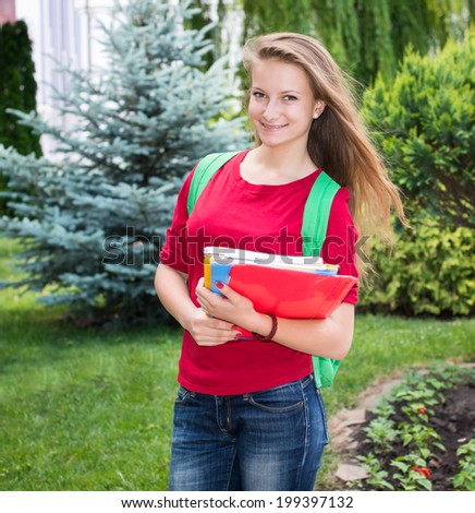 Student girl outside in summer park smiling happy. College or university student young woman with school bag.  - stock photo