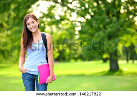 Student girl portrait holding books wearing backpack outdoor in park smiling happy going back to school. Asian female college or university student. Mixed race Asian / Caucasian young woman model. - stock photo