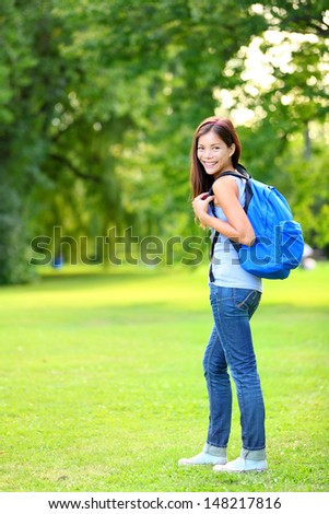 Student girl portrait wearing backpack outdoor in park smiling happy going back to school. Asian female college or university student in full length. Mixed race Asian / Caucasian young woman model.