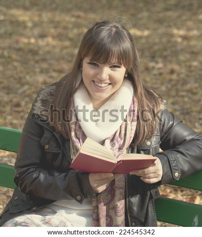 Student girl reading book on bench in autumn forest - stock photo