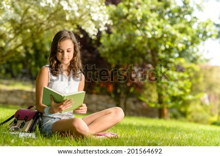 Student girl reading book sitting on grass in summer park