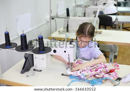 Student girl sews small dress at white sewing machine in classroom with many machines.