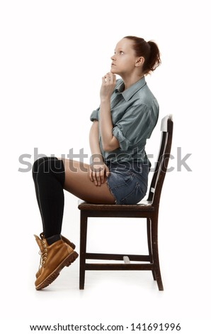 Student girl sitting on a chair, irony, drama - stock photo
