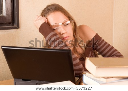 Student girl sleeoing with books and laptop in her room - stock photo