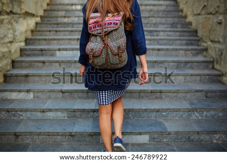 Student girl with a backpack climbing stairs. Rear view - stock photo
